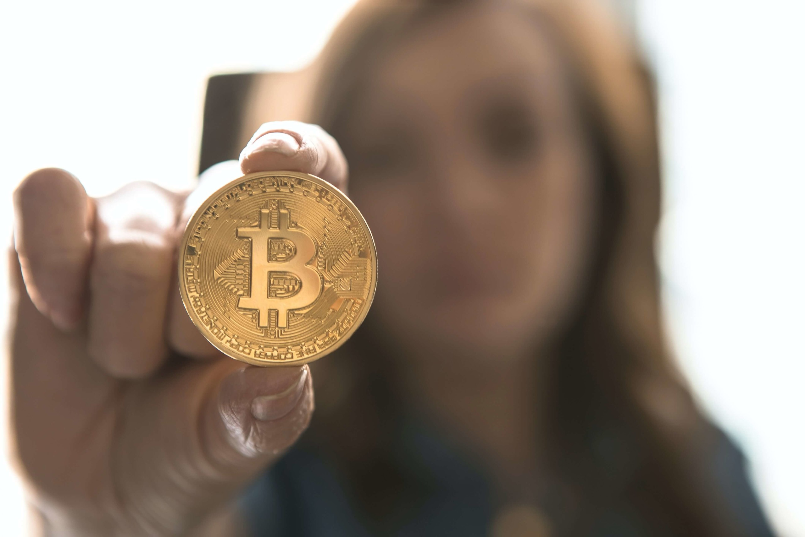 Person holding up bitcoin to represent processing digital and crytocurrency.